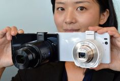 "A Japan's electronics giant Sony employee displays the new concept digital camera ""Cyber-shot DSC-QX100"" (L) and ""Cyber-shot DSC-QX10"", call..."