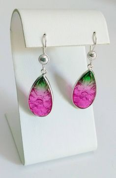 These earrings feature large carved bi-color stones bezel set in sterling silver. The watermelin quartz stones are paired with silver shield earwires.  The pink and apple green transparent stones are 1.25 x .5 inches. They are set in a sterling silver bezel with 925 sterling silver jump rings and earwire findings.  These earrings have carved flowers on the front and back of the quartz stones.