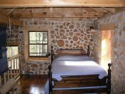 The upstairs bedroom is surrounded by thick cordwood walls and large windows.