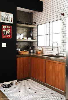 Cozinha industrial tem parede pintada de preto, piso com pastilhas em formato hexagonal, subway tiles e bancada e prateleiras de concreto.