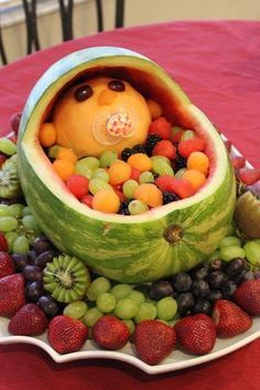 Baby shower fruit arrangement. Get a melon baller to scoop out the watermelon and cantaloupe or other melon. I made the baby's head out of the end of a peeled cantaloupe, with blueberries as eyes. It turned out cute!
