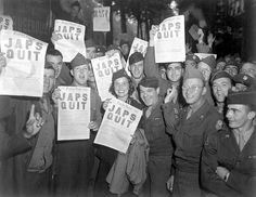 """GI's at the Rainbow Corner Red Cross Club in Paris, France, whoop it up after buying the special edition of the Paris Post, which carried the banner headline, """"JAPS QUIT"""". August 10, 1945."""