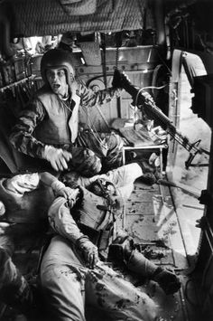 A mortally wounded comrade at his feet, Lance Cpl. James C. Farley, helicopter crew chief, yells to his pilot after a firefight in Vietnam, 1965.
