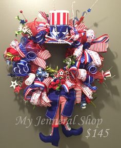 """This is such a fun and patriotic wreath that can be used for Memorial Day, Fourth of July, Veteran's Day, or just year round. This wreath is 28"""" wide and 38"""" from hat to toe. It's really full of ribbon and all sorts of fun stars and stripes. $145"""