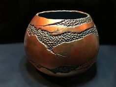 This gorgeous bowl has been hand painted and hand carved from a dried gourd by SeBour Designs. This wood like bowl features a multi colored metallic faux copper finish. Beautiful golds, bronze, copper, and hints of reds will compliment any decor. Hand carved to resemble cracked and aged pottery.