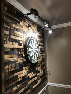 Built a backer for my dart board using Shou Sugi Ban; a Technique of burning wood to preserve it. I cut up pieces of plywood and burnt them at different levels to create the contrast. The lighting was also all home made with plumbing parts and G10 light sockets with LED bulbs. Very happy with the end result! Please repin!