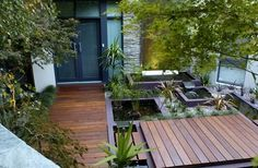 small courtyard space used well. Beautiful garden design with decking and water.   adamchristopherdesign.co.uk