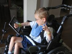 iPad on articulating arm from RJ Cooper mounted on front of wheelchair for child