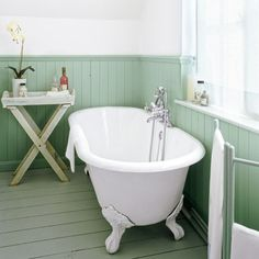 Sage-green paint unifies the pine floorboards with the baseboards and wainscoting, lending this bare-bones bath a serene, airy feeling. | Photo: David Palmer/IPC Images | thisoldhouse.com