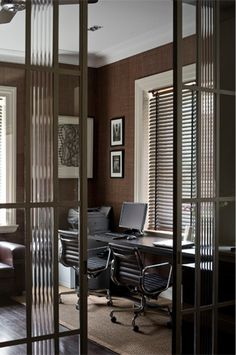 Modern art deco home office - love the reed glass in the doors and the surprising use of the grass cloth wallpaper.