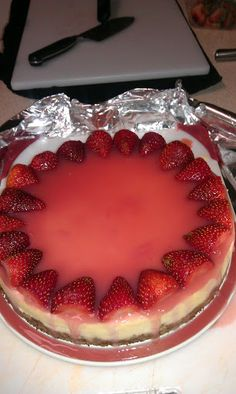 1 1/2cup - Graham crakers  2tbsp - Sugar  3tbsp - Butter or margarine -- melted  FILLING:    19oz - Cream cheese -- softened  1cup - Sugar  2tsp - Lemon peel -- grated  1/4tsp - Vanilla  3each - Eggs  GLAZE:    1cup - Mashed strawberries  1cup - Sugar  3tbsp - Cornstarch  1/3cup - Water