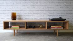 This stylish piece is made to order. Can be used as a TV Stand, Coffee table, Bookcase, or anything you want.  Made with solid white oak. No veneers,