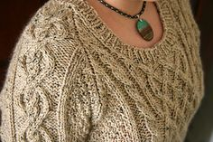This beautiful cabled scoop-neck sweater is knit in the round from the bottom…