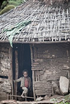 Africa |  People.  A young boy photographed in the doorway of his home, in Rira, Bale Mountains, Ethiopia.