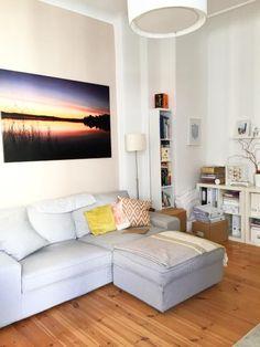 Schönes Wohnzimmer in Berliner Wohnung. Graues Sofa, Holzdielen, weißes Bücherregal. Wohnung in Berlin-Charlottenburg