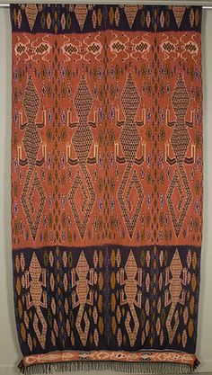 "Hinggi  Sumba. Indonesia  48""x 110""plus fringe  Warp ikat. Cotton.  This striking ikat was unfortunately too long for my photo wall. The wide dark alligator border and narrow strip border at the bottom are repeated at the top. This man's shoulder cloth or sarong is probably 20 to 30 years old. It was dyed with the traditional indigo and kombu"