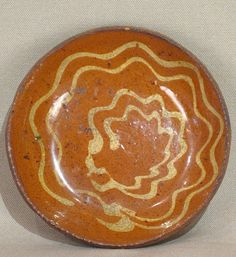 "Slip Decorated Redware Plate Mid-Atlantic States, Circa 1860 	Local Red Clay, White Slip, and a Clear Lead Glaze…An unpredictable and charming Redware Plate…slip decorated in a folky stylized flower motif which envelops the entire interior surface…there is an appealing contrast between the Red glaze ground and the Yellow slip…also there are two one inch tight hairlines at "" 10 and two ""…Otherwise the Condition is Very Good…the bottom shows wear from use.....~♥~"