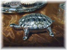 Verzilverd pillendoosje in de vorm van een schildpad met een mini pincet voor de pillen die ook het staartje vormt.