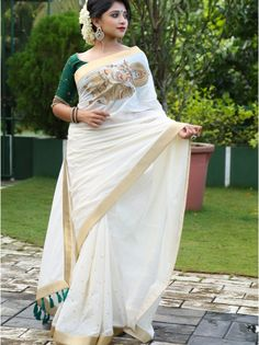 Kerala Silk Saree in White Color With Green Tassel This drape is enhanced with Krishna embroidery on chest area along with 2 inch gold border all around and white brocade facing worn over with white bottle green round neck blouse, Onam Saree, Kasavu Saree, Handloom Saree, Kerla Saree, Saree Poses, Kerala Saree Blouse Designs, Saree Blouse Patterns, Traditional Sarees, Traditional Dresses