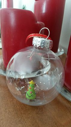 Clear ornament with clay tree inside.