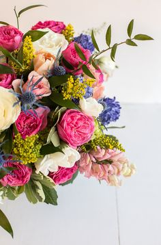 A colorful floral centerpiece with garden roses, hyacinth, thistle, stock, and more.