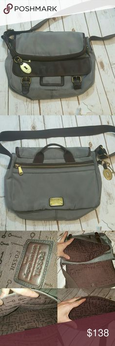 "Fossil gray nylon and brown leather messenger bag Pockets galore: 2 on front, flap is one big pocket, back has big pocket, 3 on inside of bag. No rips, holes, or stains. Leather shows some natural wear. Strap is 35"" fully extended. Has all original hardware, i.e. Key and faux lock. Also has leather carrying handle, if you don't want to use the crossbody strap. Width- 13.5"" Height- 9.5"" Base is 4"" wide. Fossil Bags Laptop Bags"