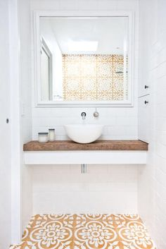 Love this small bathroom design with floating white counter topped with unfinished reclaimed wood counter top, small white basin sink, wall-mounted silver sink faucet, and gorgeous dark yellow, tan and white printed Spanish-inspired tiles on the floor and wall of the shower.