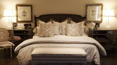 Stunning master bedroom design with caned headboard, taupe and cream bed linens, mirrored chests, louis chair, lucite lamps, decorative pictures and upholstered bench