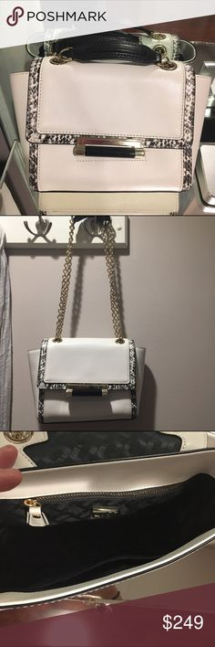 Diane Von Furstenberg white leather cross body This DVF crossbody is an everyday bag that can go from casual to dress. The chain is gold plate with black leather straps, allowing you to double or single strap it. The shape is gorgeous and one of a kind! The interior lining is in perfect condition. Purchased from Bloomingdales in Fashion Valley Mall in San Diego. Comes with dust bag. Price is firm. Diane von Furstenberg Bags Crossbody Bags