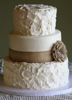 Rustic wedding cake with burlap ribbon and flower.