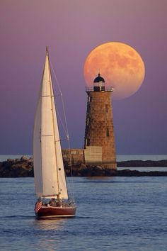 Beautiful, peaceful picture of boat on the water with lighthouse and big beautiful moon…