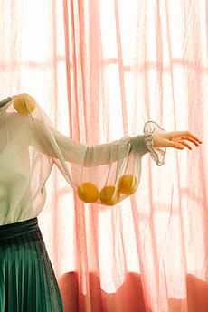 editorial fashion colorful photograph of woman wearing sheer green blouse with lemons in the sleeve in front of pink sheer curtains.