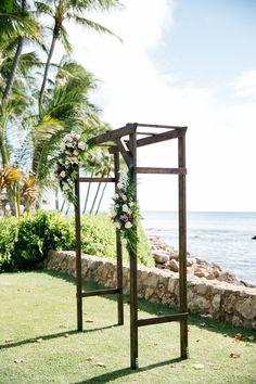 Dark wood wedding arbor, tropical seaside wedding ceremony, purple and white florals // Makai Creative
