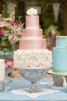 tall wedding cake with pearl pink fondant and white ruffled floral layer