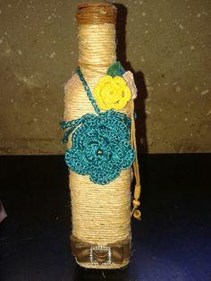 Artes de Léo, garrafa revestida com sisal e flores de crochê no acabamento