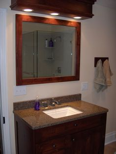 Bathroom Remodel: framed standalone mirror, single faucet sink, dark wood cabinets, stone counter top