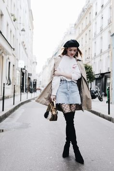 Paris Outfits and Tips in a light blue denim skirt, fishnet tights, and over-the-knee black boots.   Sea of Shoes