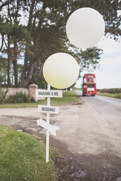 Wooden Direction sign with giant white balloons - Image by Katy Melling Photography - Jenny Packham 'Willow' gown for a beach wedding at Newton Hall in Northumberland with a pink rose bouquet by Katy Melling Photography.