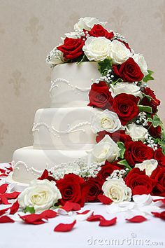 A wedding cake decorated with red and white roses.