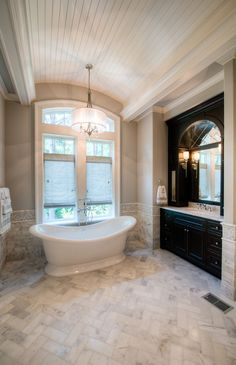 Beautiful bathroom.  Love the black vanity with gray marble.  Love the light fixture over the tub