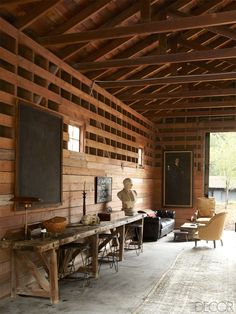 blank board on wall.    In the Romantic Barn, an American workbench holds a Poul Henningsen lamp and a Belgian bust; the stools are French,the portrait is 19th century, the antique rug is Persian, and the redwood walls are original.     Southern California Horse Ranch - Ellen DeGeneres Portia de Rossi Santa Monica Home - ELLE DECOR