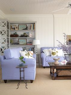Simple yet chic styling turns this sunroom into an escape. White walls, trim, and beaded board ceiling keep the sunroom feeling bright and cheerful, regardless of the sun's location. Shelves in one corner of the room add storage for books and display space for beach decor. New lavender slipcovers on the couches match the hydrangeas in the backyard, bringing an element of the outdoors in.