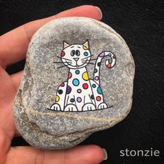 Whimsicle painted rock of a cat with colorful spots! Painted Rock Animals, Painted Rocks Craft, Hand Painted Rocks, Painted Stones, Pebble Painting, Pebble Art, Stone Painting, Stone Crafts, Rock Crafts