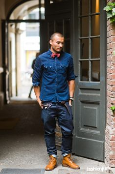 Shop this look on Lookastic: http://lookastic.com/men/looks/denim-shirt-jeans-brogue-boots-bow-tie-belt-watch/11267 — Red Plaid Bow-tie — Blue Denim Shirt — Silver Watch — Dark Brown Leather Belt — Navy Jeans — Tan Leather Brogue Boots