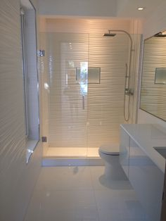 All white bathroom...gorgeous! Wall tile, toilet, vanity and shower column by Porcelanosa.