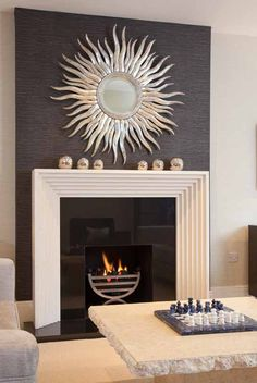 Black feature chimney breast with sunburst mirror and cream fireplace. More