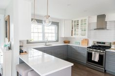 A gray and white kitchen makeover using IKEA cabinetry, marble like quartz countertops, subway tile backsplash, and gold hardware. A timeless, bright and classic kitchen design / renovation! Click through to the blog for the full source list and how-to's!