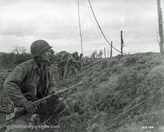 WWII, 1944 - Infantryman of the 47th Infantry Regiment, 9th Infantry Division hunker down behind an embankment while they wait for the order to advance near Hucheln, Germany, November 26, 1944.