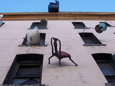 """Built by artist Brian Goggin in 1997, """"Defenestration,"""" is a rather shocking work of public art that generally surprises out-of-towners wandering through SoMa. Renovated last year, the artsy building houses a street art gallery and provokes the question: """"What if an upholstered chair was cast as Spiderman?"""""""