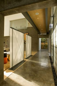 Intexure Architects The hallway of the same house also employs a complex layering of volume and material. The freestanding translucent scre...